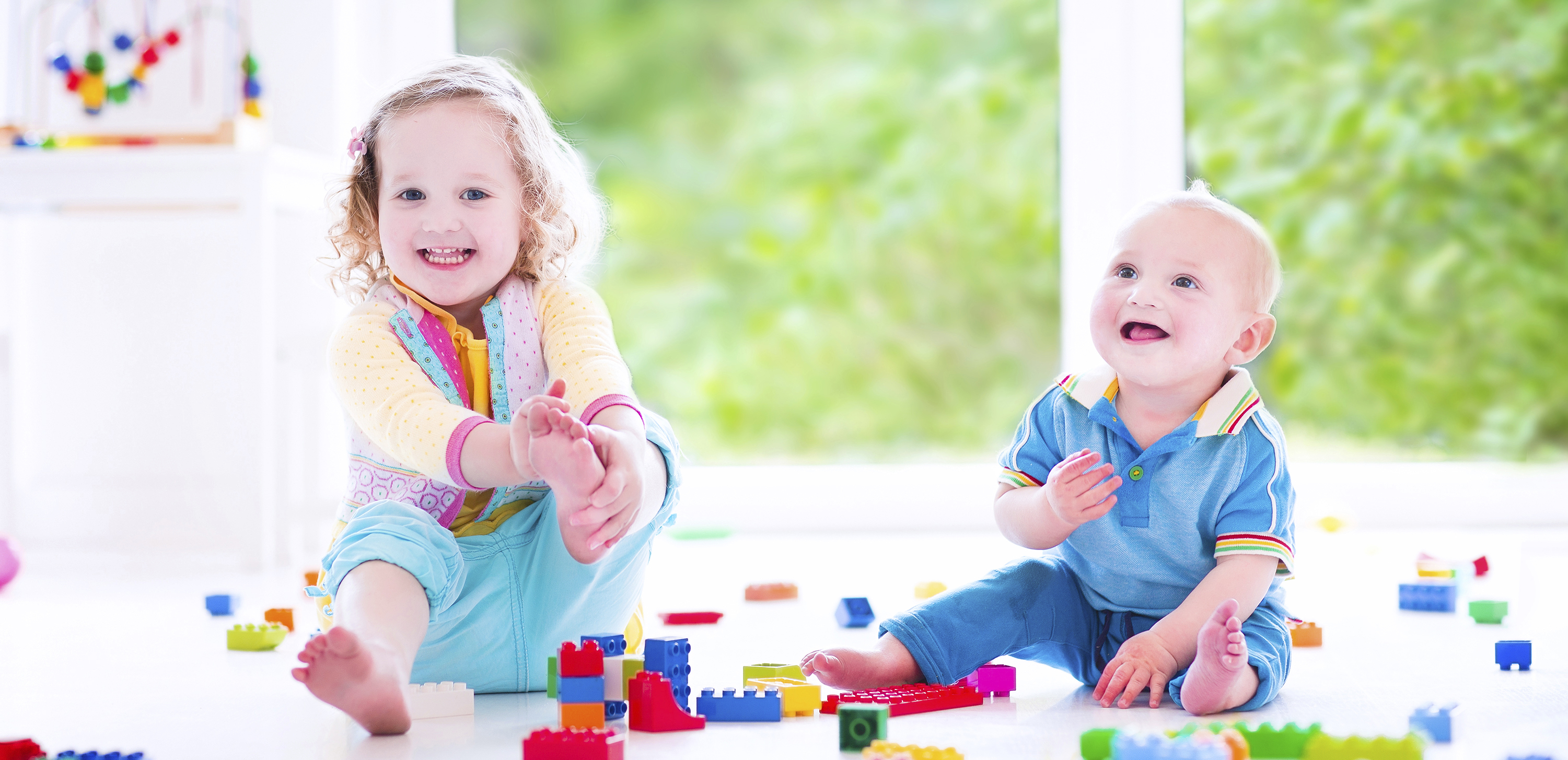 Adorable laughing toddler girl and a funny little baby boy playing with colorful blocks sitting on a floor in a sunny bedroom with a big window
